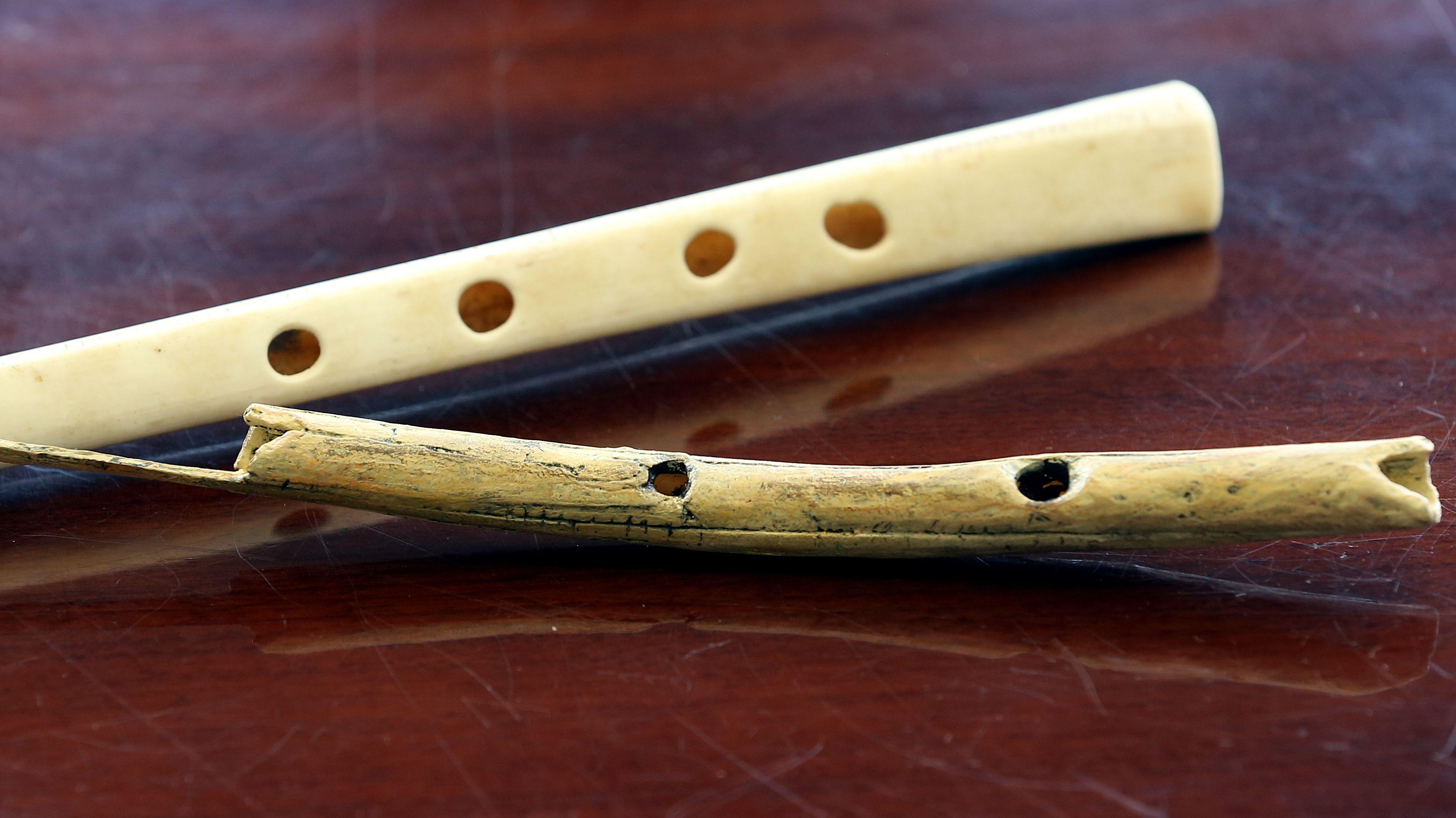 Der Nachbau einer 38000 Jahre alten Flöte aus Geierflügelknochen (oben) und eine Flöte aus Mammutelfenbein liegen am 30.07.2015 auf einem Tisch des Archäologen Instituts in Berlin