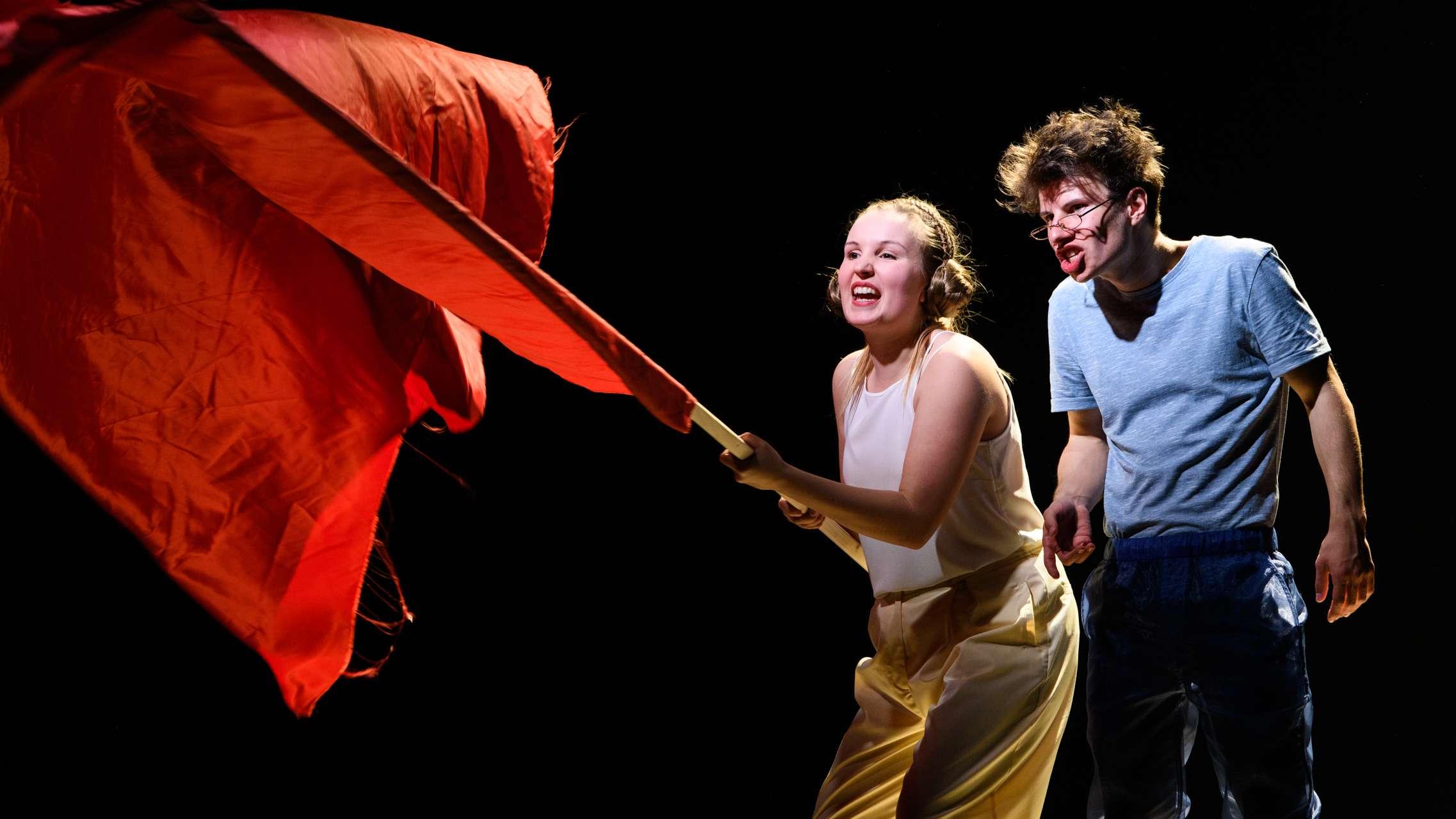 Zwei Schauspieler auf der Bühne, die Frau schwingt eine rote Fahne.