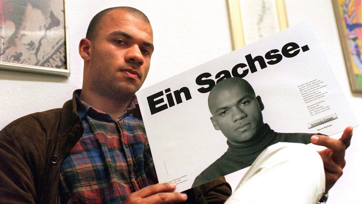 """Samuel Meffire mit einem Aufklärungs-Plakat gegen Ausländerfeindlichkeit. Unter der Überschrift """"Ein Sachse."""" ist darauf sein Gesicht abgebildet"""