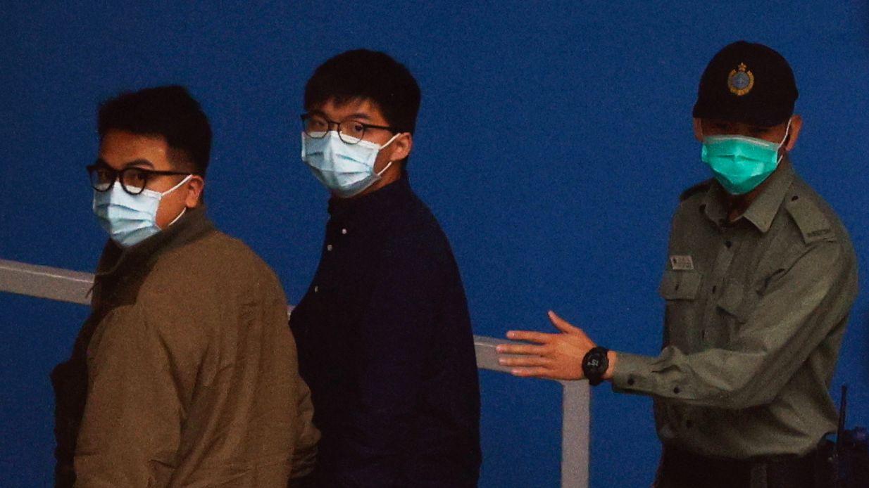 Die Aktivisten Ivan Lam (l.) und Joshua Wong (m.) auf dem  Weg zum Gericht