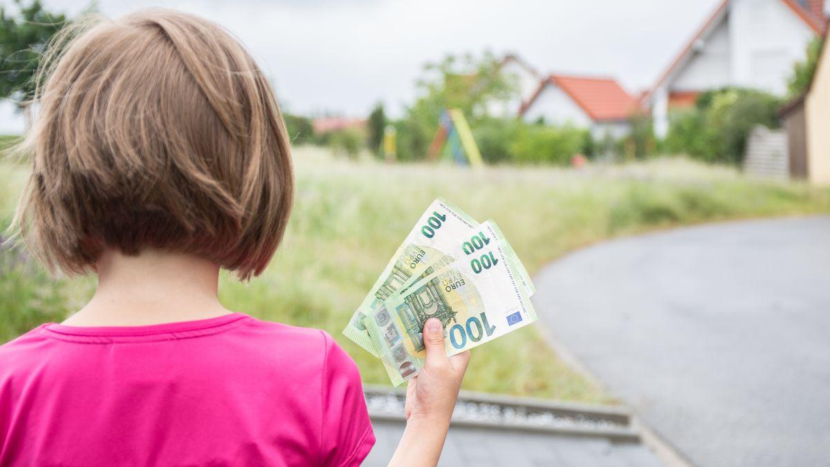 Ein Kind hält drei Hundert-Euro-Scheine in der Hand.