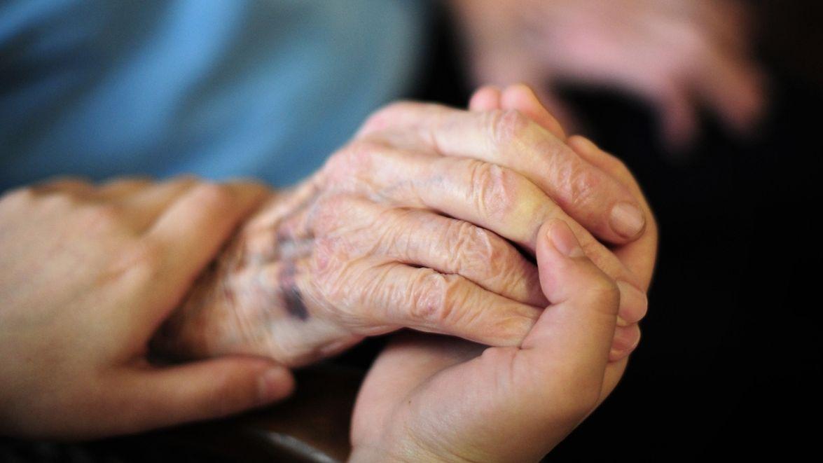 Pfleger hält Hand einer Frau