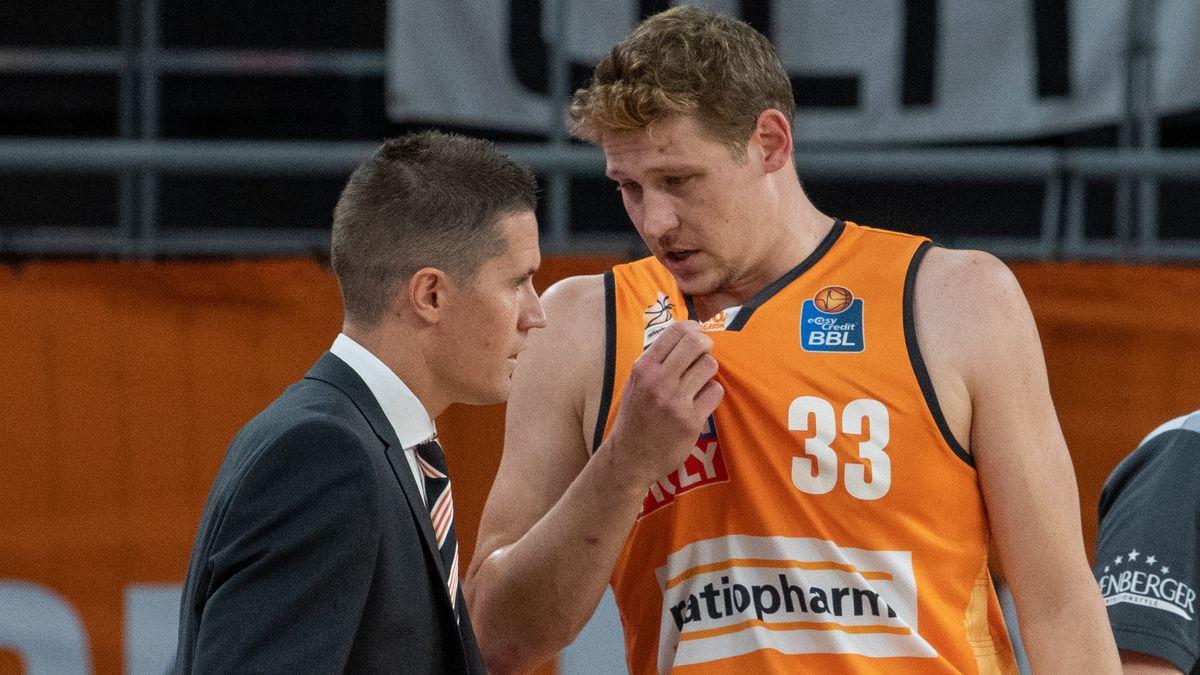 Patrick Heckmann im organgenen Basketball-Trikot mit der Nummer 33 redet mit Ulms Trainer Jaka Lakovic.