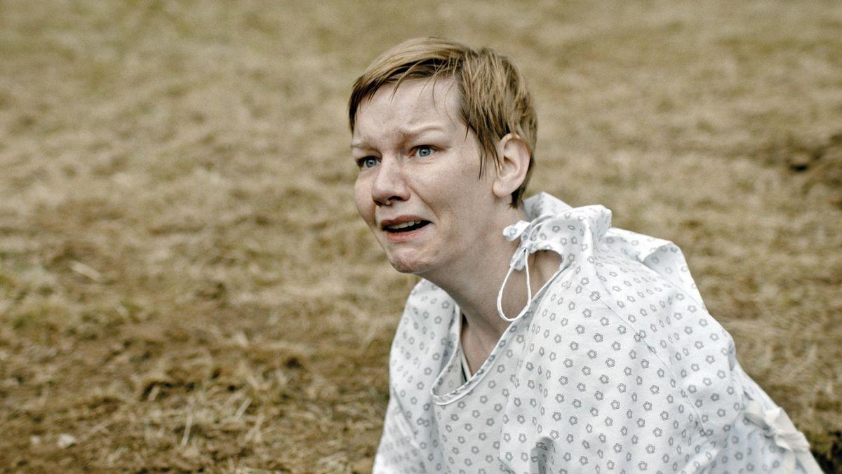 """Offenkundig verwirrte Frau im Krankenhaushemd draußen auf lehmigen Boden: Sandra Hüller in dem Film """"Schlaf"""""""