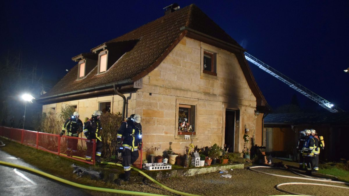Feuerwehrleute stehen vor einem Haus, dessen Fassade zum Teil vom Ruß schwarz verqualmt ist.