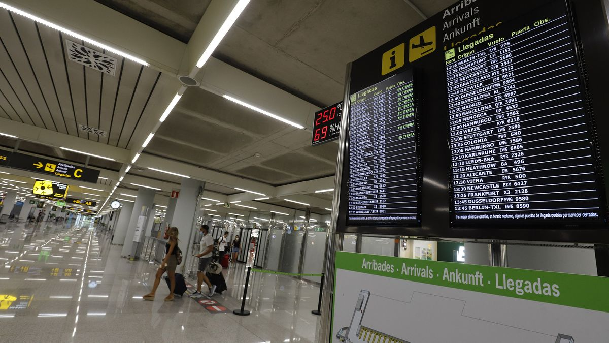 Der fast leere Flughafen auf der Insel Mallorca, im Vordergrund eine Tafel, die über ankommende Flüge informiert, im Hintergrund vereinzelte Touristinnen.