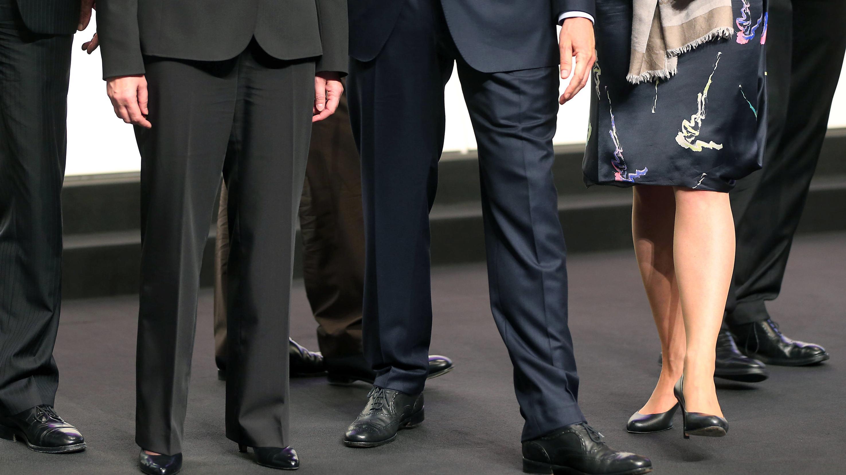 Die Beine von vier Männern in Anzügen und zwei Frauen in Kleid und Hosenanzug