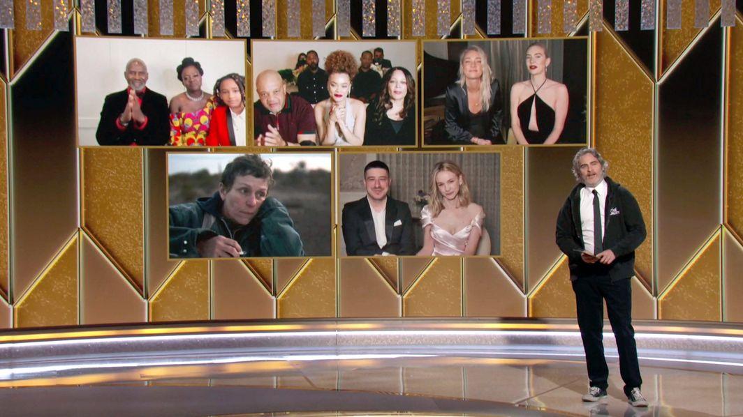 """Das vom TV-Sender NBC veröffentlichte Foto zeigt Schauspieler Joaquin Phoenix, der die Kategorie """"Beste Schauspielerin in einem Filmdrama"""" bei den Golden Globe Awards 2021 auszeichnet, während die Nominierten Viola Davis (oben, l-r), Andra Day, Vanessa Kirby, sowie Frances McDormand (unten, l-r) und Carey Mulligan auf einer Leinwand zu sehen sind."""