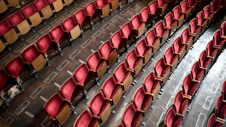 Theatersitze von oben, rot gepolstert, leer.