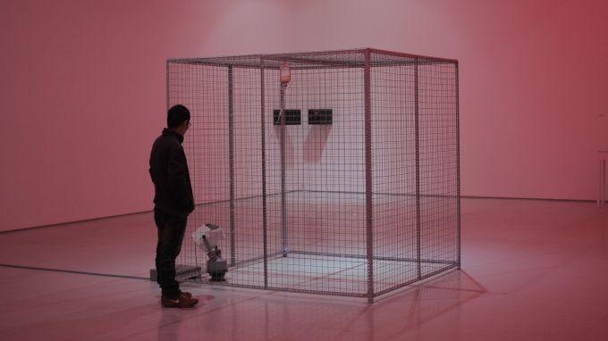 """Ein mannsgroßer quadratischer, komplett vergitterter Kasten, in dem eine Seifenblasenmaschine Seigenblasen versprüht, die am Gitter zerplatzen: Die Installation """"Cannot Help Them"""" von Chen Hangfeng"""