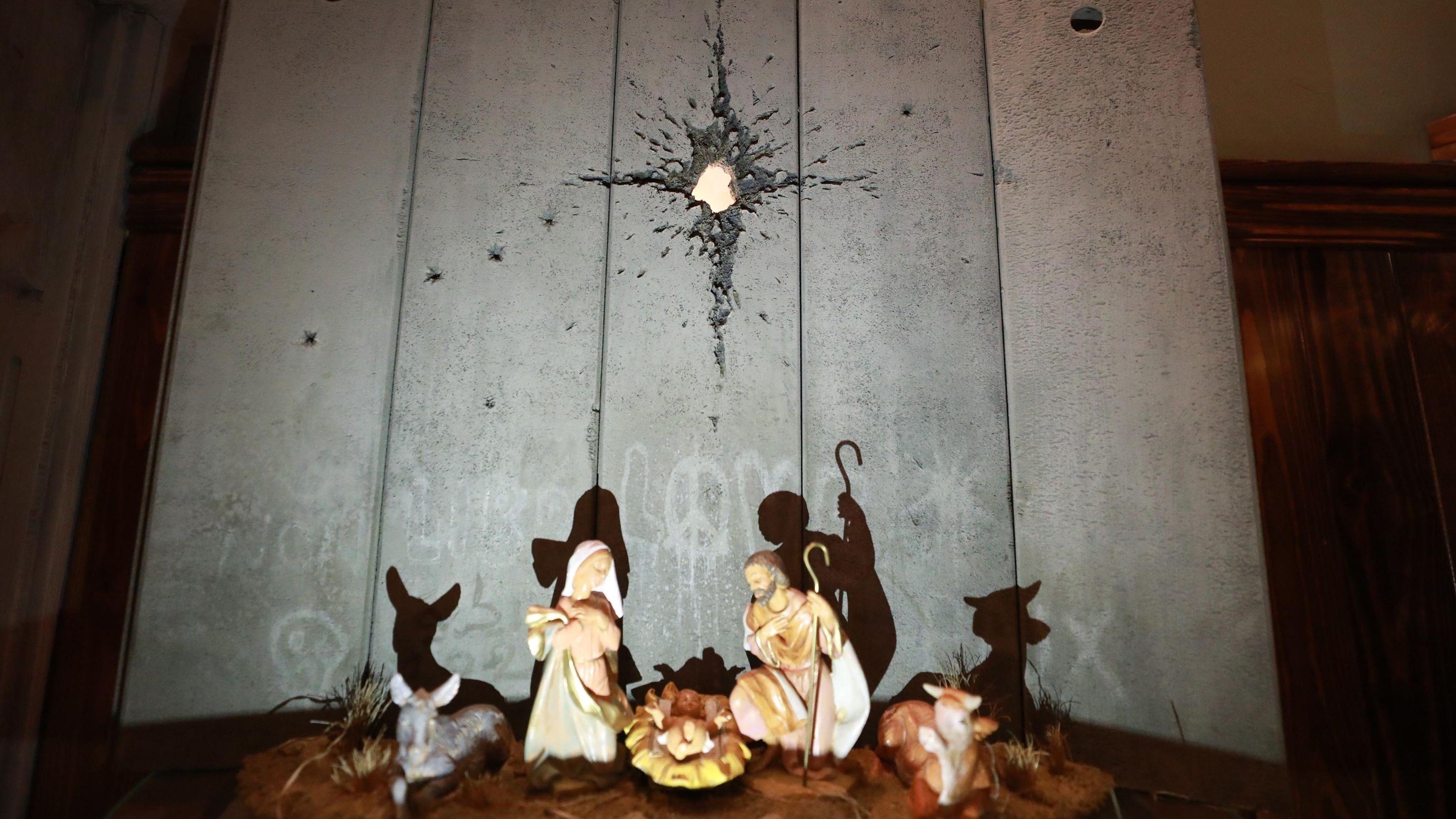 Maria und Josef, Ochs und Hirte und das Jesuskind vor einer durchschossenen Beton Mauer: Installation von Banksy