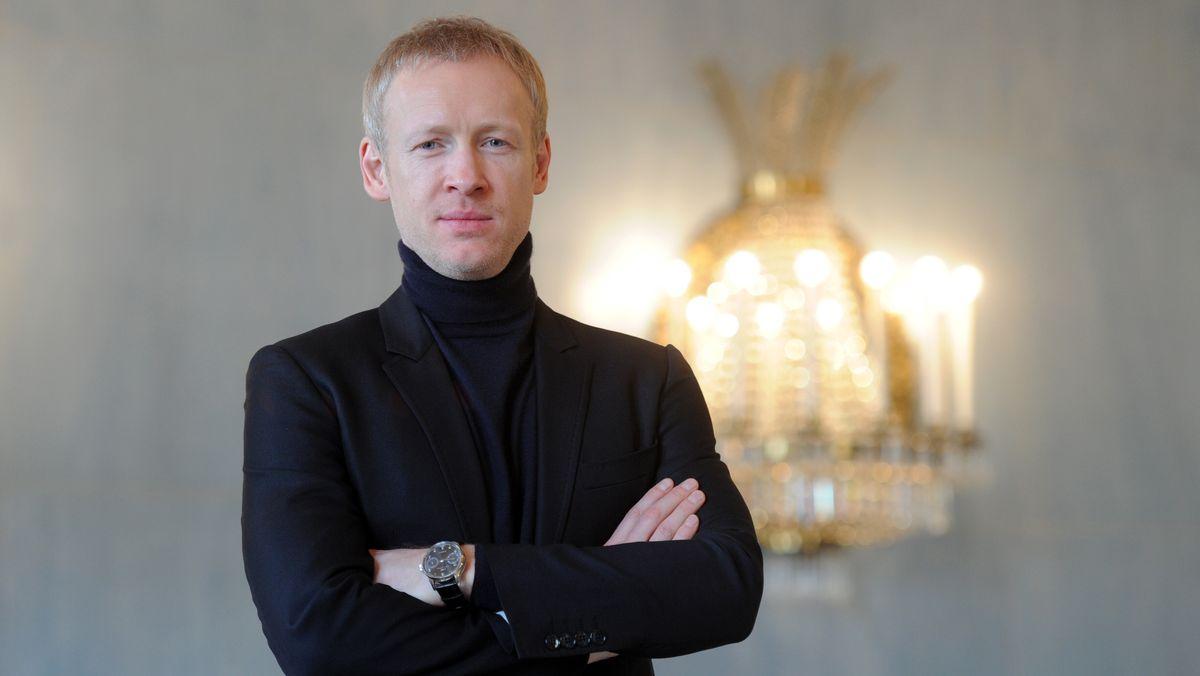 Igor Zelensky steht vor Wand mit funkelnder Lampe, er blickt in die Kamera und hat die Arme vor dem Oberkörper verschränkt.