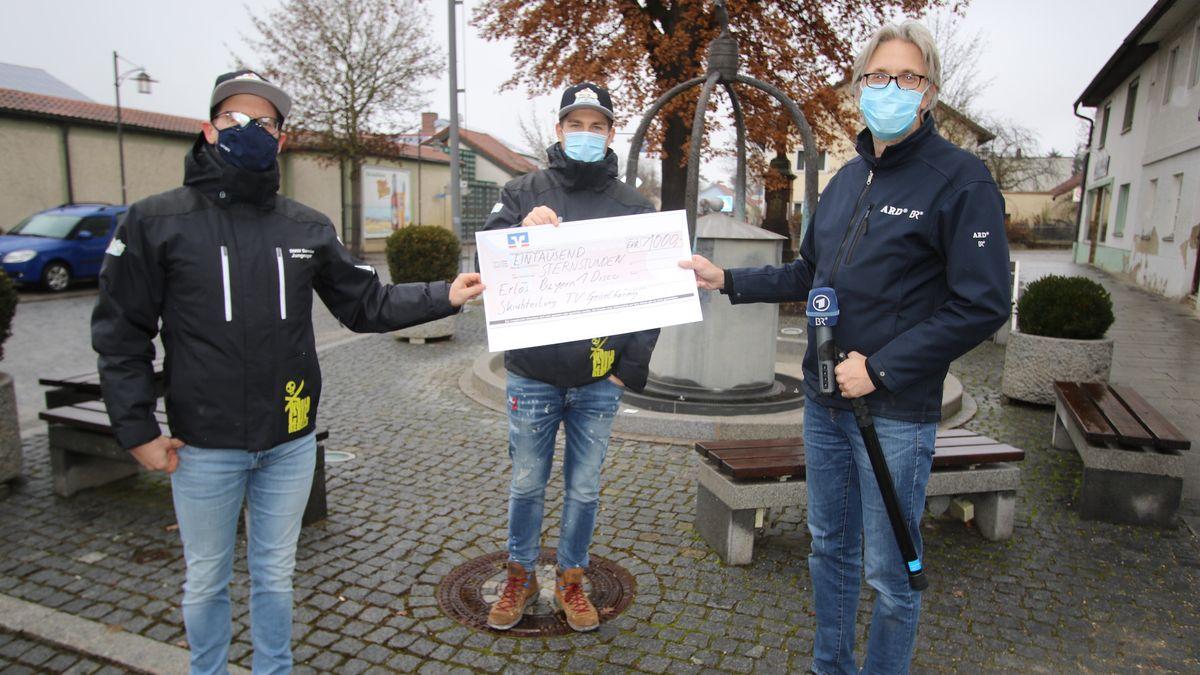 Drei Männer halten einen Spendenscheck