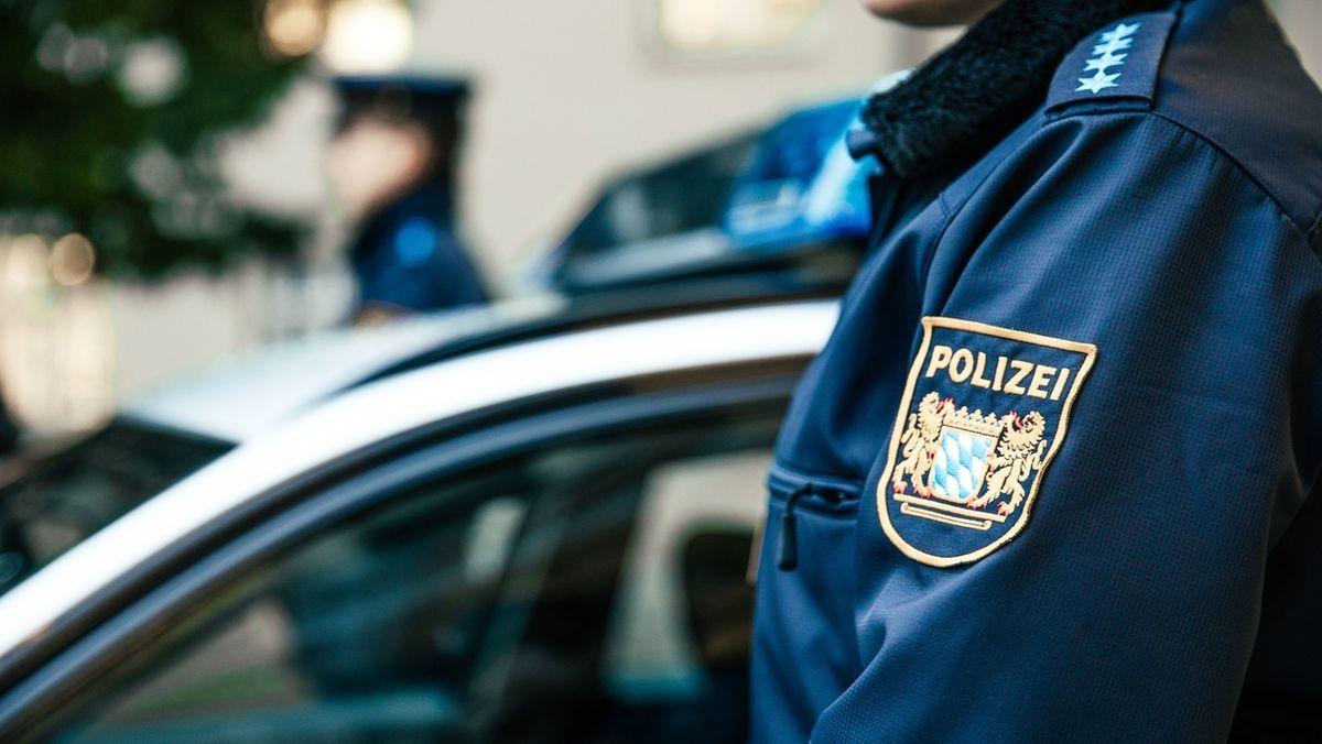 Eine Polizistin und ein Polizist stehen vor dem Eingang eines Polizeipräsidiums  vor einem Polizeiauto mit Blaulicht (Symbolbild)