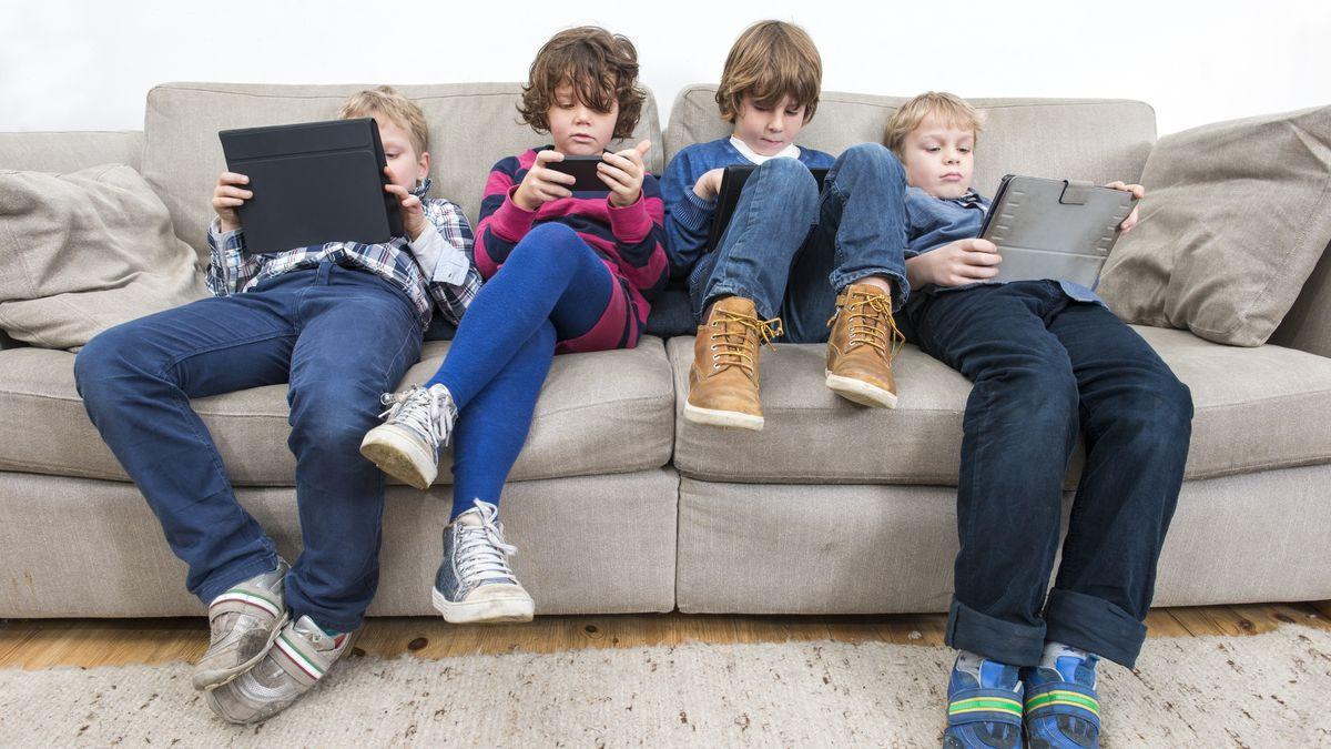 Vier Kinder sitzen auf der Couch und beschäftigen sich mit Laptop, Tablet und Smartphone.