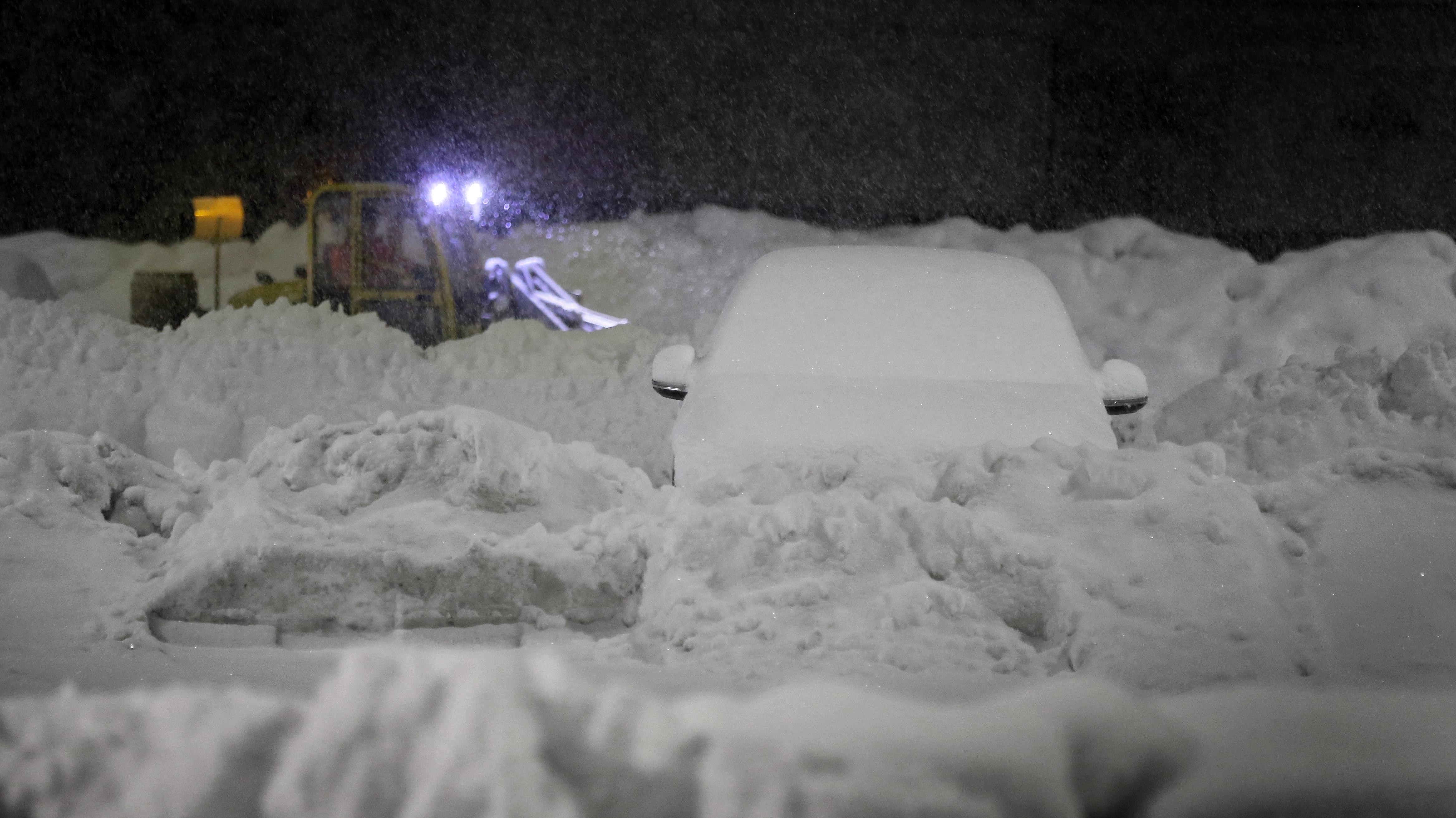 Ein Räumfahrzeug befreit den Parkplatz eines Supermarktes in Kaufbeuren vom Schnee (Archivbild).