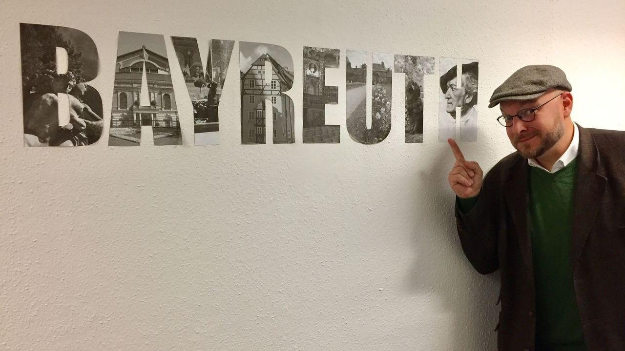 """Hannes Schott steht vor einem Schriftzug """"Bayreuth"""""""
