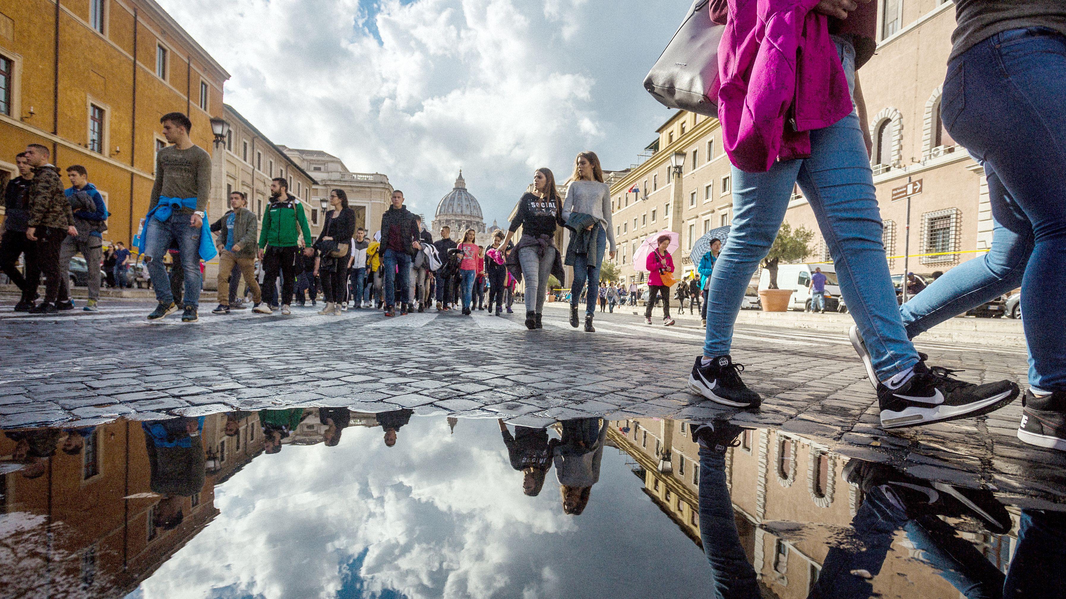 Menschen gehen an der Via della Conciliazione in Rom entlang. Der Petersdom ist im Hintergrund zu sehen.