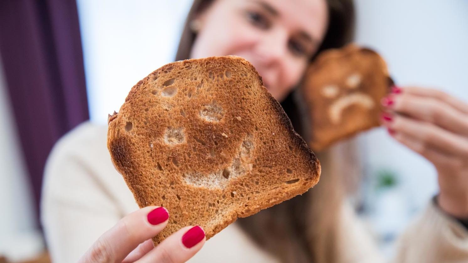 Eine junge Frau hält zwei Scheiben Toastbrot mit eingeritzten Gesichtern in den Händen.