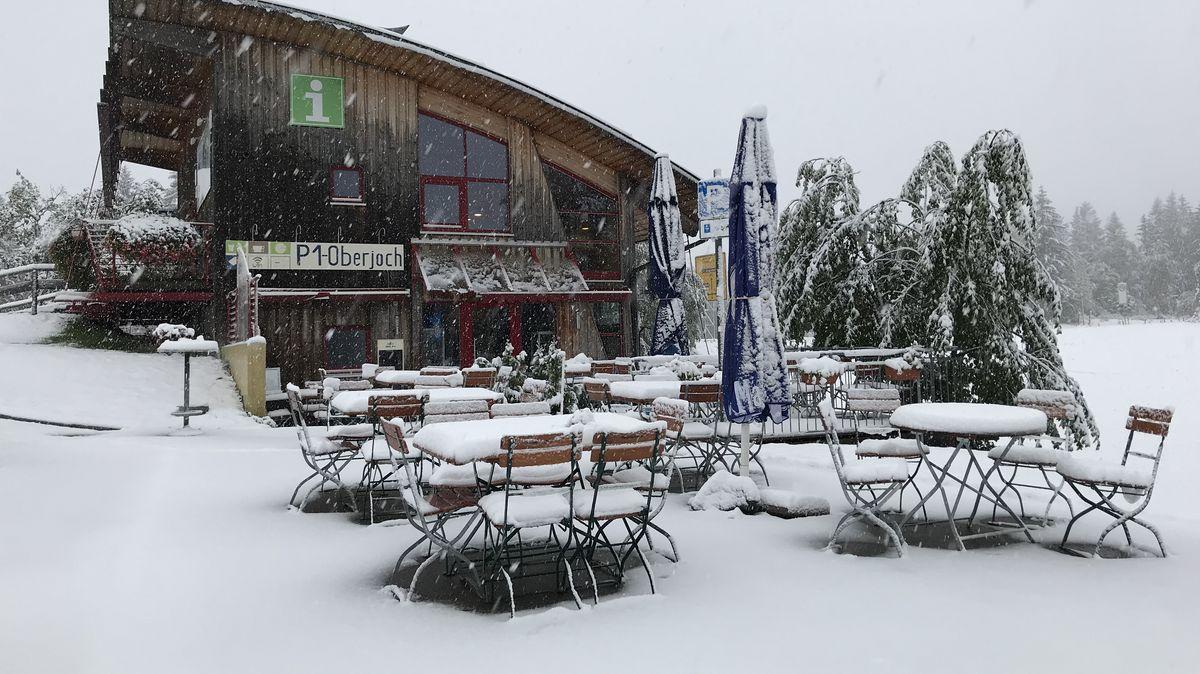 Schneebedeckte Wirtsgartentische und Stühle.
