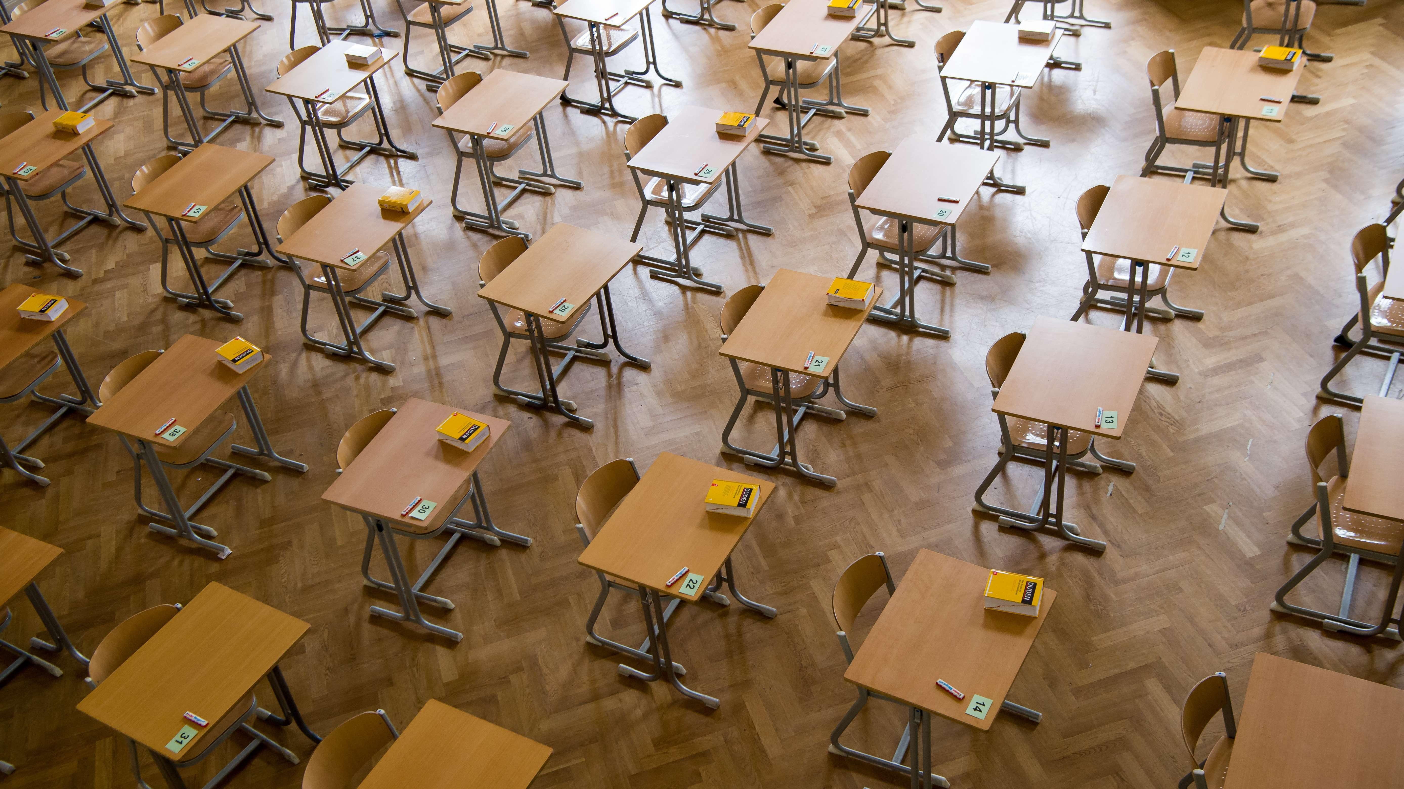 Durchnummerierte Tische stehen in Reihe und Glied: In der Schule werden Abiturprüfungen abgehalten