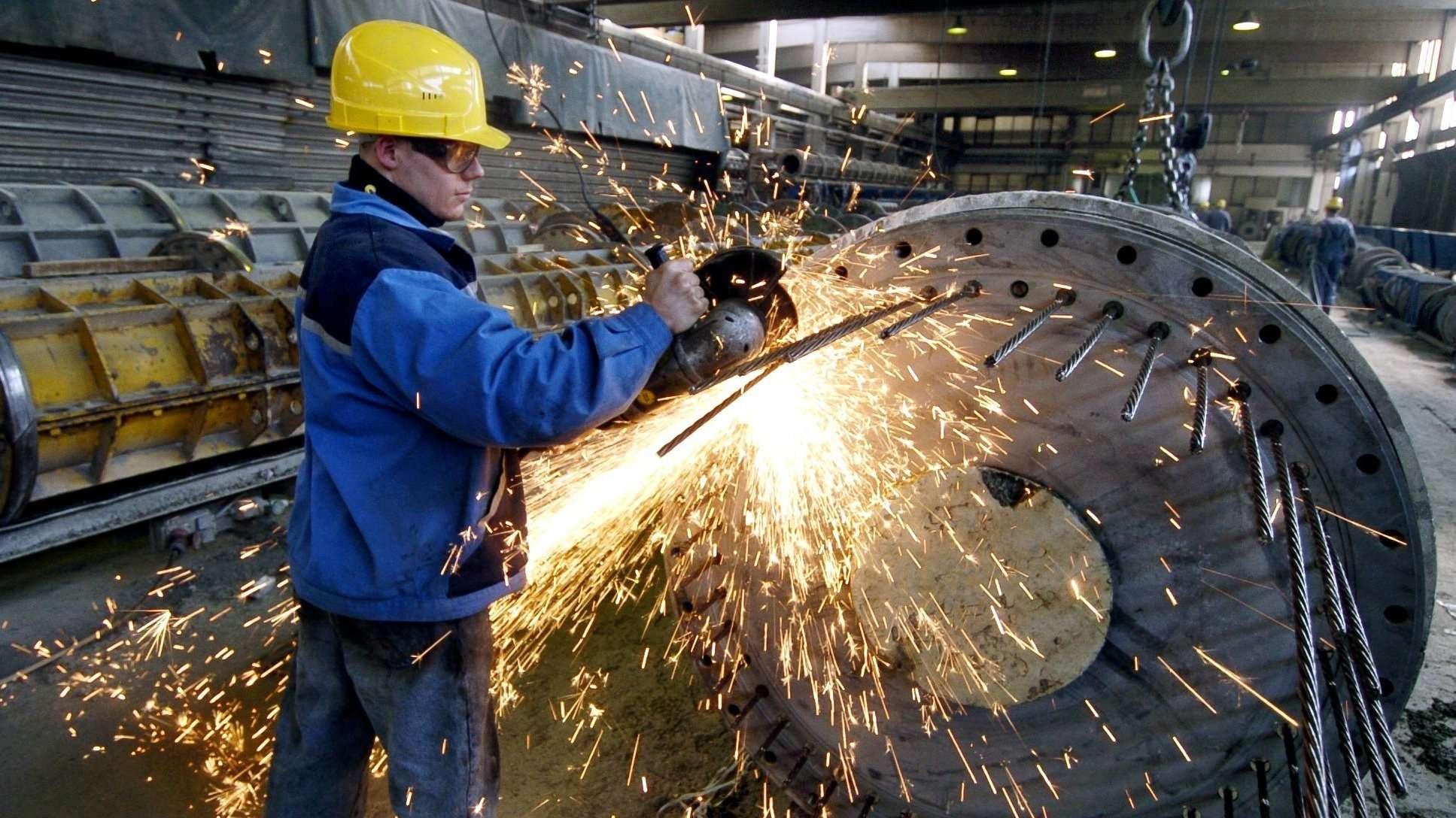 Ein Mitarbeiter befestigt auf dem Werksgelände im oberpfälzischen Neumarkt Drähte an einer Form für einen Betonmast.