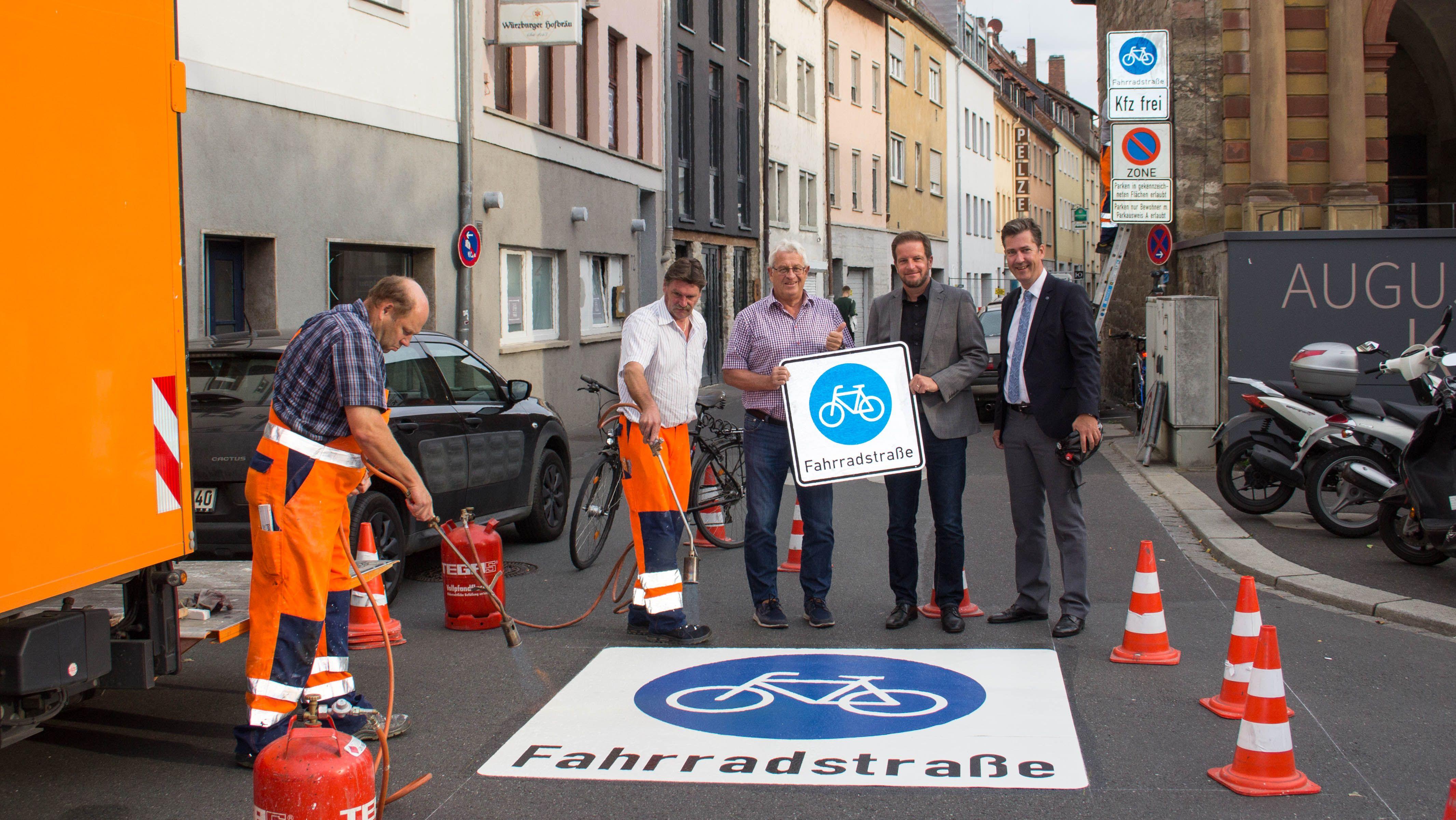 v.l.n.r.: Oberbürgermeister Christian Schuchardt, Baureferent Benjamin Schneider, Tiefbau-Chef Jörg Roth in der neuen Fahrradstraße. Die beiden Mitarbeiter des Bauhofs bringen gerade das Piktogramm auf der Fahrbahn auf.