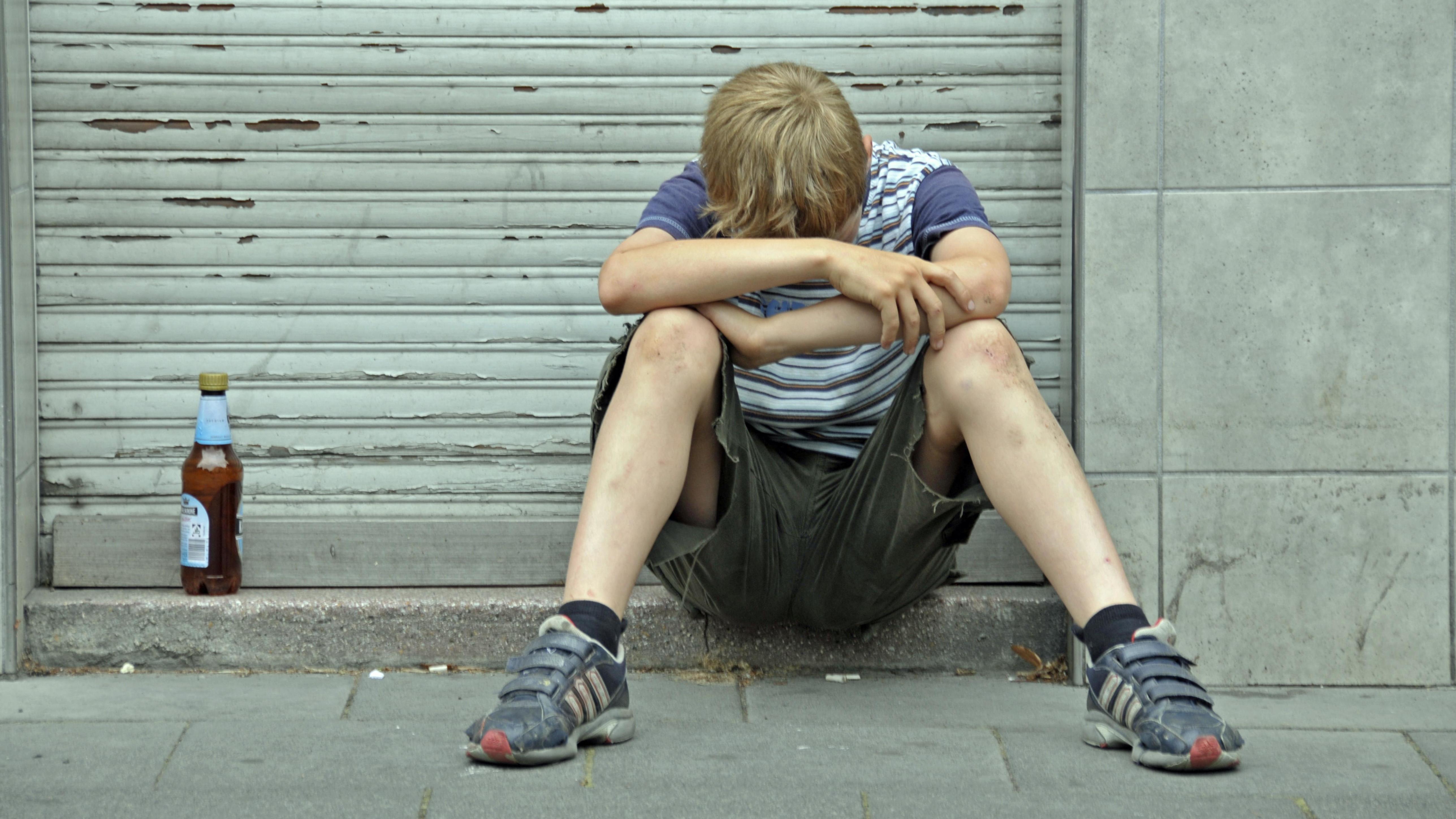 Junge sitzt neben Bierflasche vor einem geschlossenen Laden, den Kopf auf die Arme gelegt