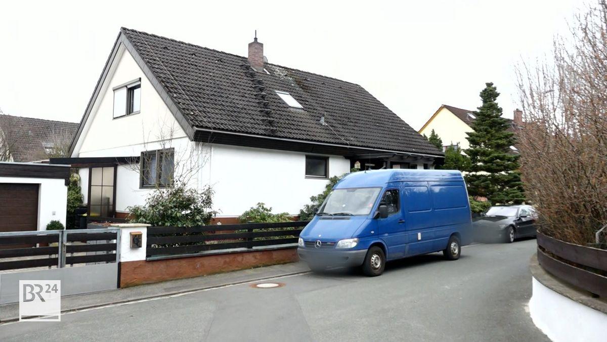 Vor einem Haus parkt ein blauer Kastenwagen