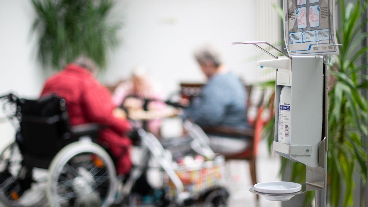 Desinfektionsmittelspender im Vordergrund, hinten zwei ältere Damen, eine davon im Rollstuhl