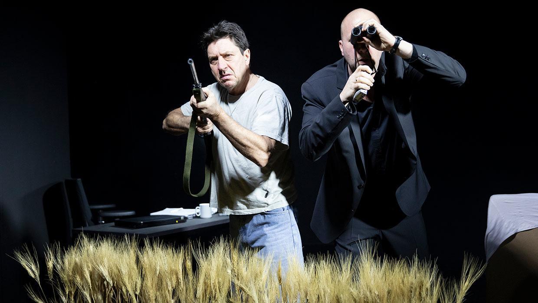 Zwei Männer mit Gewehr und Feldstecher