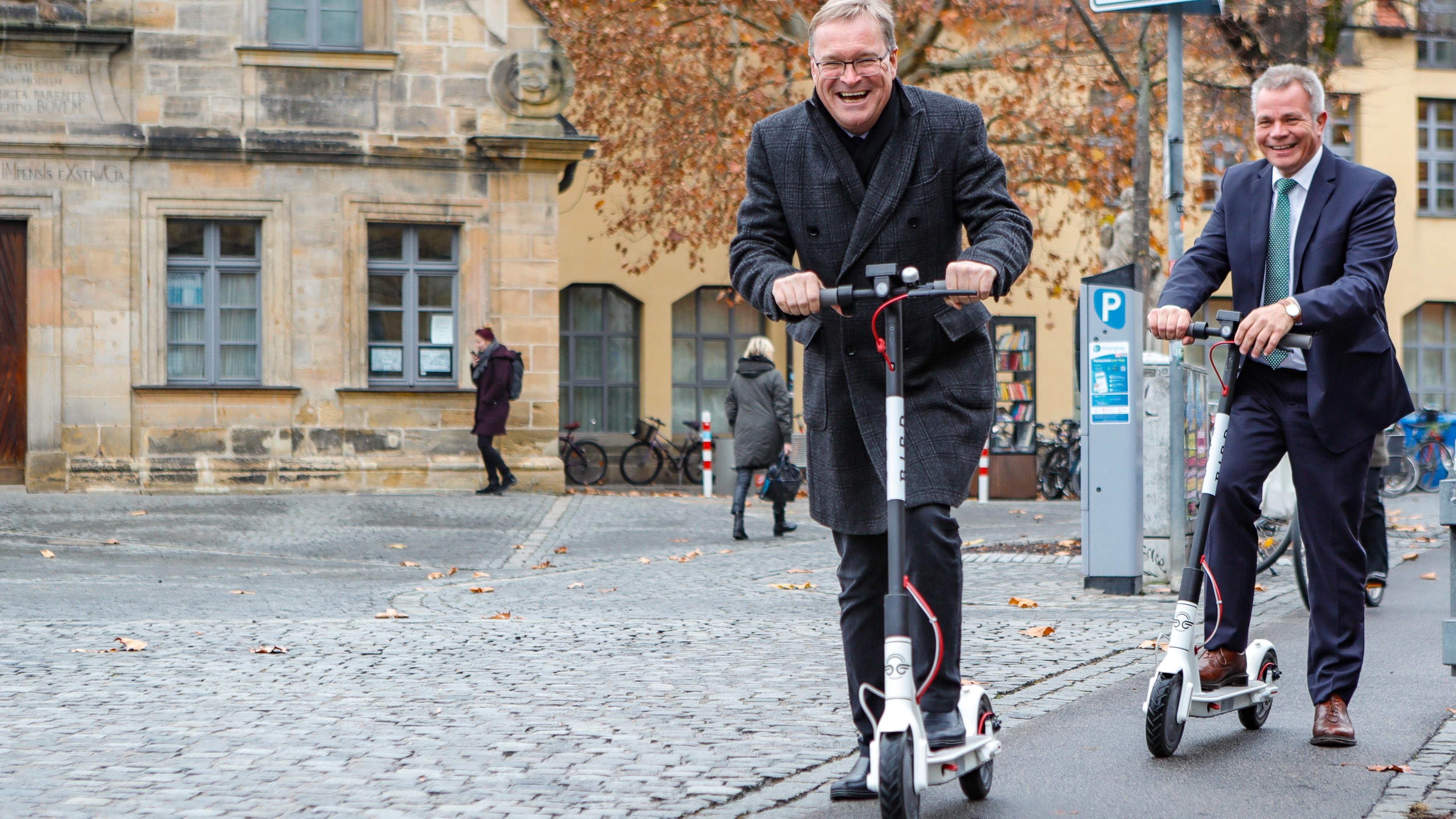 """Bambergs Oberbürgermeister Andreas Starke (vorne) und Stadtwerke-Geschäftsführer Michael Fiedeldey testen die E-Scooter am Bamberger """"Kranen""""."""
