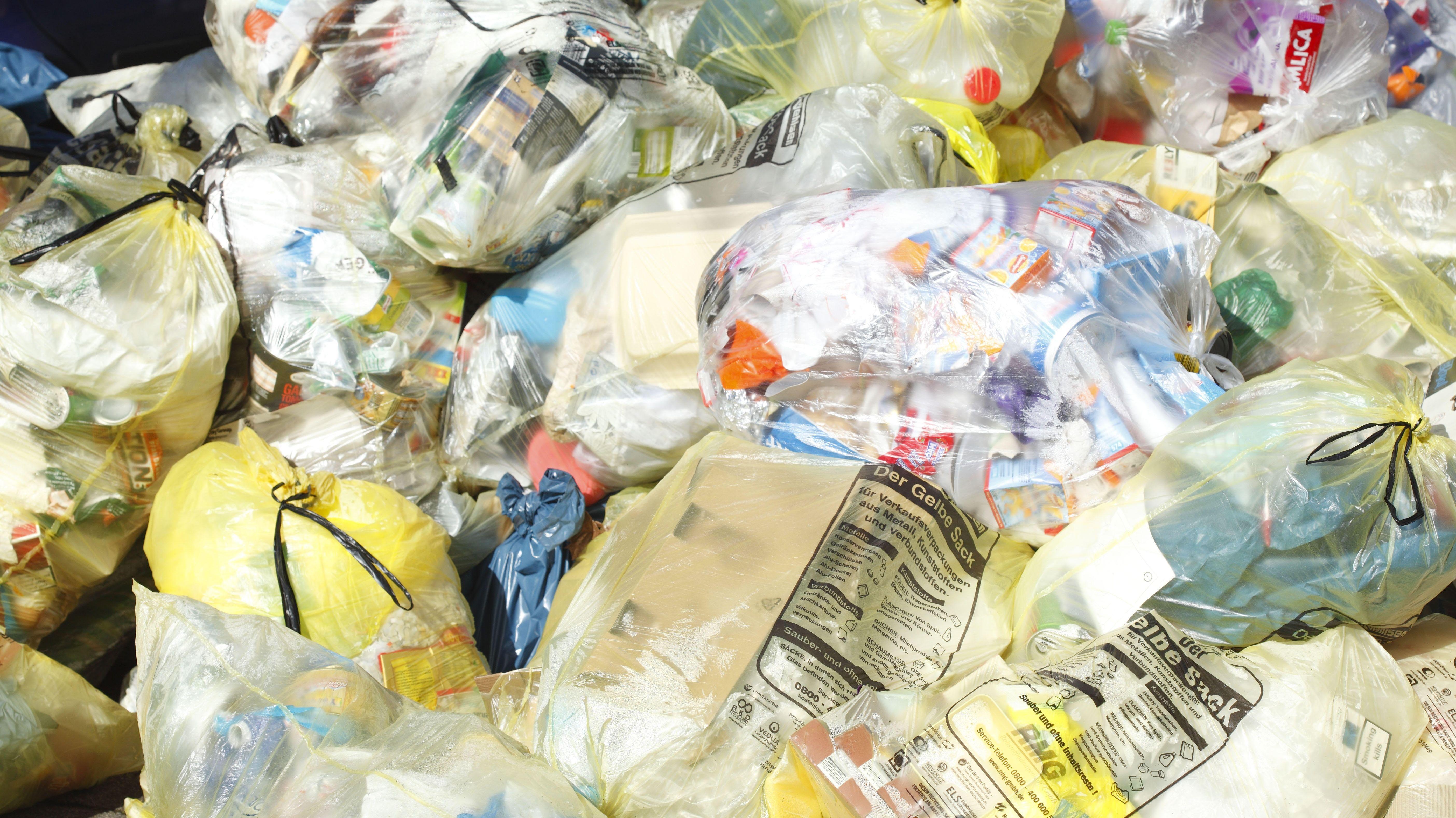 Gelbe Säcke mit Plastikmüll am Straßenrand.