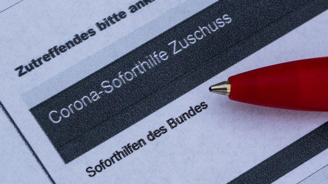 in Stift liegt auf einem Antrag für den Corona-Soforthilfe-Zuschuss.
