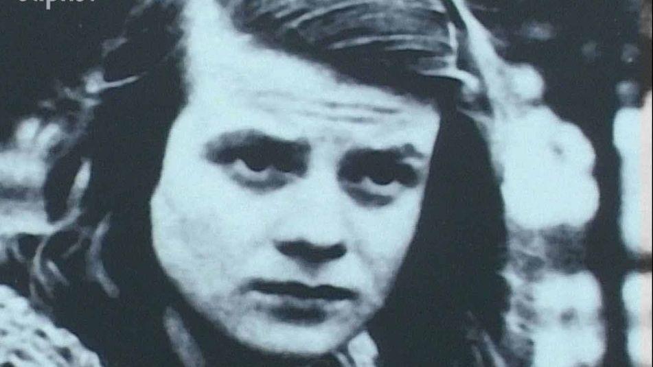 Eine blaustichige Fotografie einer jungen Frau mit Seitenscheitel und ernstem Blick