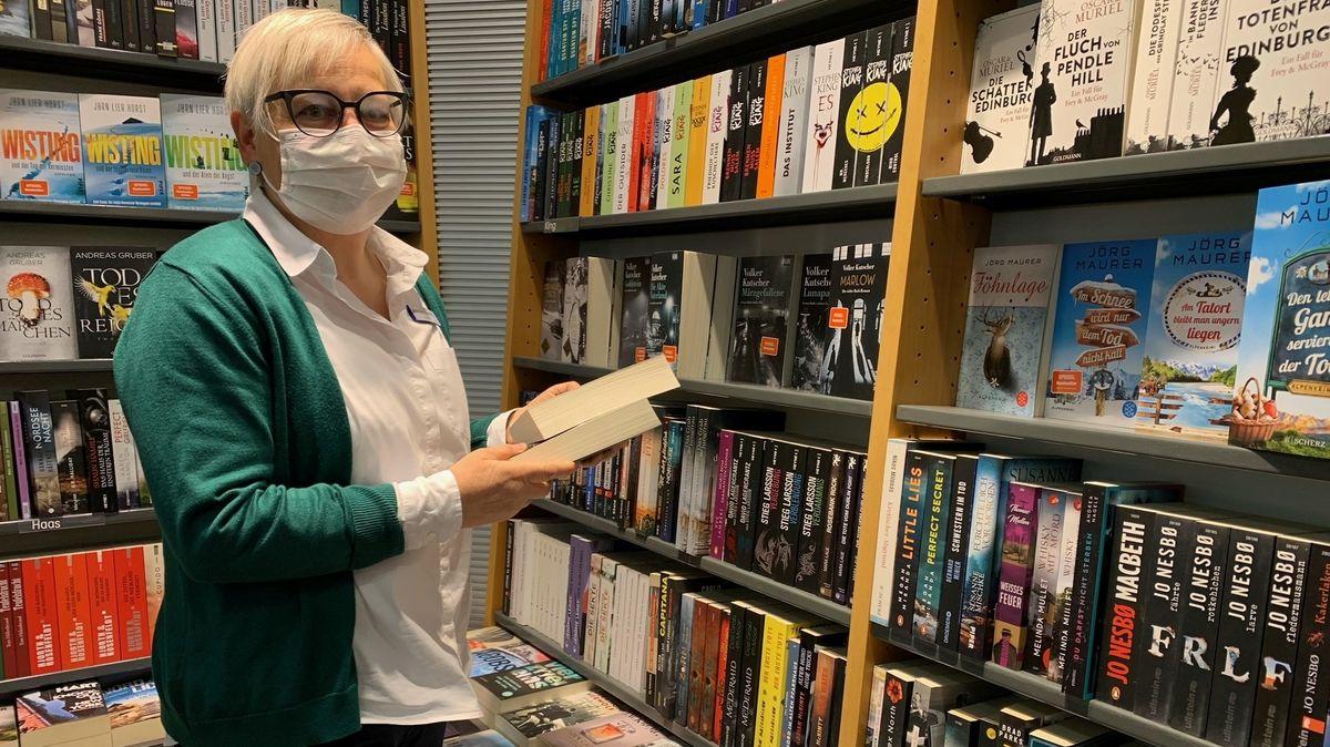 Dame mit Maske und Brille räumt Bücher in ein Verkaufsregal