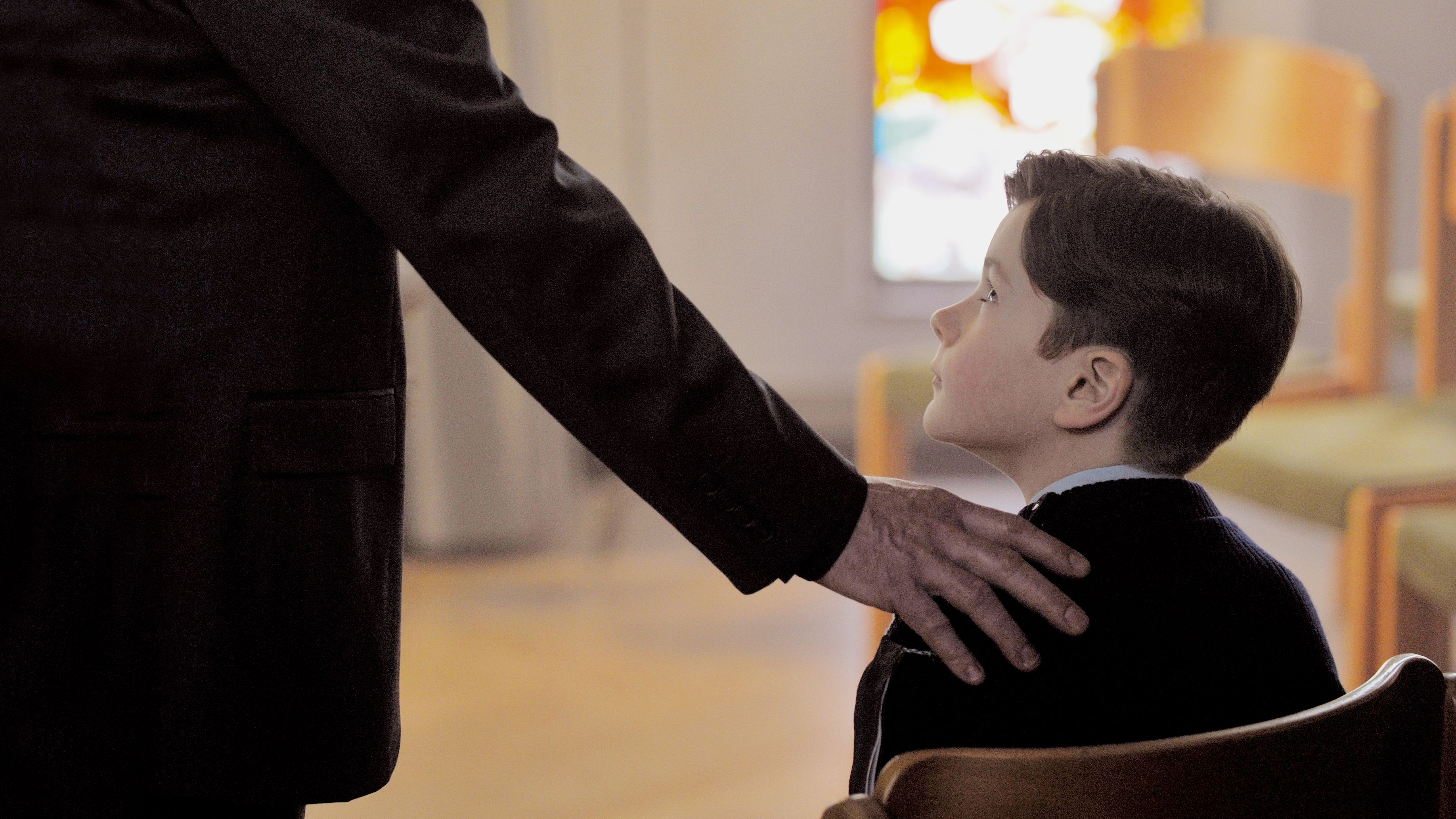 """Filmszene aus """"Gelobt sei Gott"""": Die Hand eines alten Priesters umklammert die Schulter eines kleinen Jungen (Davan Collin)"""
