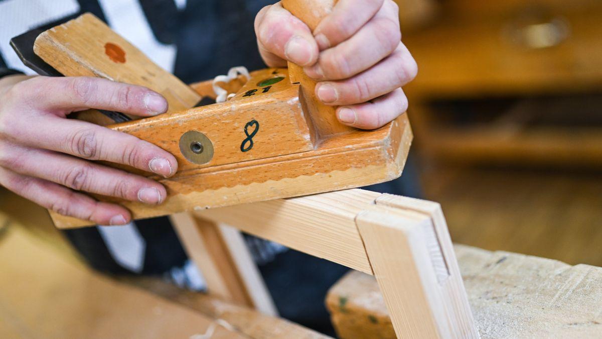 Auszubildender im Schreiner-Handwerk arbeitet an einem Werkstück.