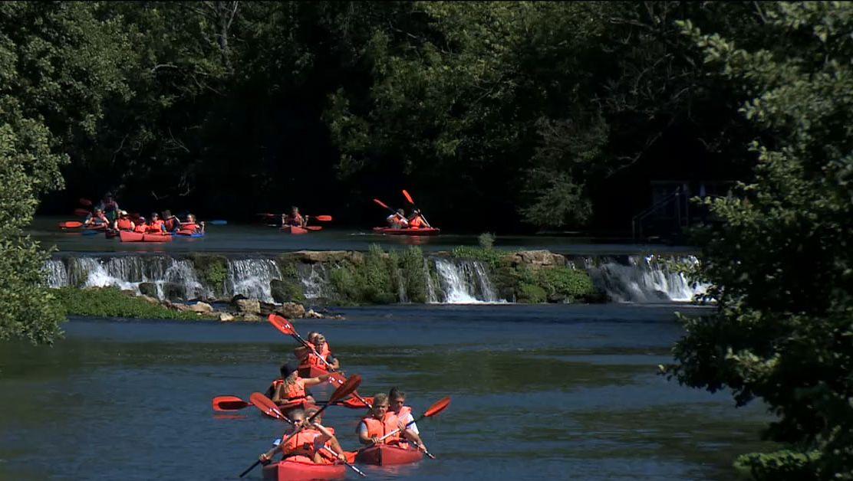 Mehrere Kanufahrer paddeln in roten Kanus auf der Wiesent, im Hintergrund dichter Wald.