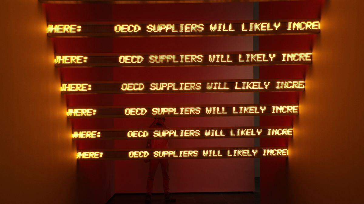 """Installation """"Red Yellow Looming"""" im Museum Met Breuer, New York: Gelbe Schrift auf roten Laufbändern in einem rot beleuchteten Raum"""