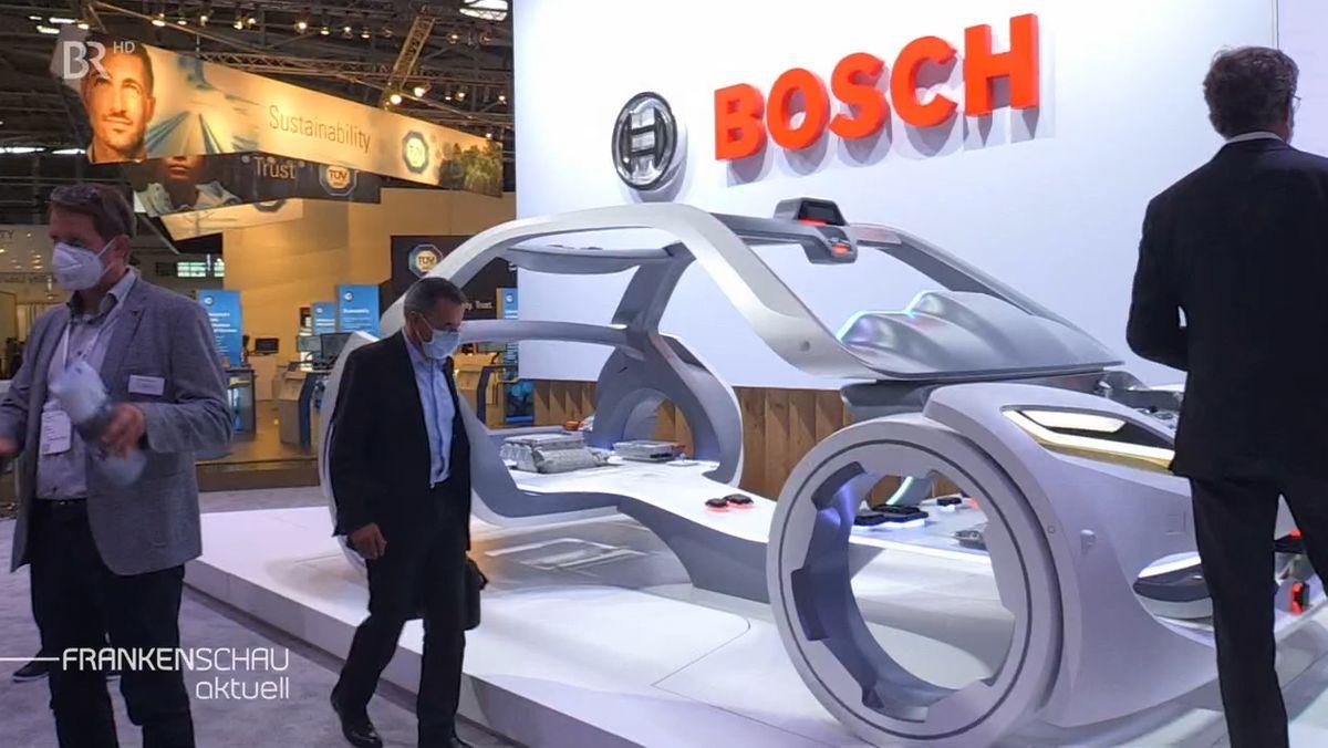 Auf einem Podium steht die Karosserie eines futuristisch aussehenden Autos.