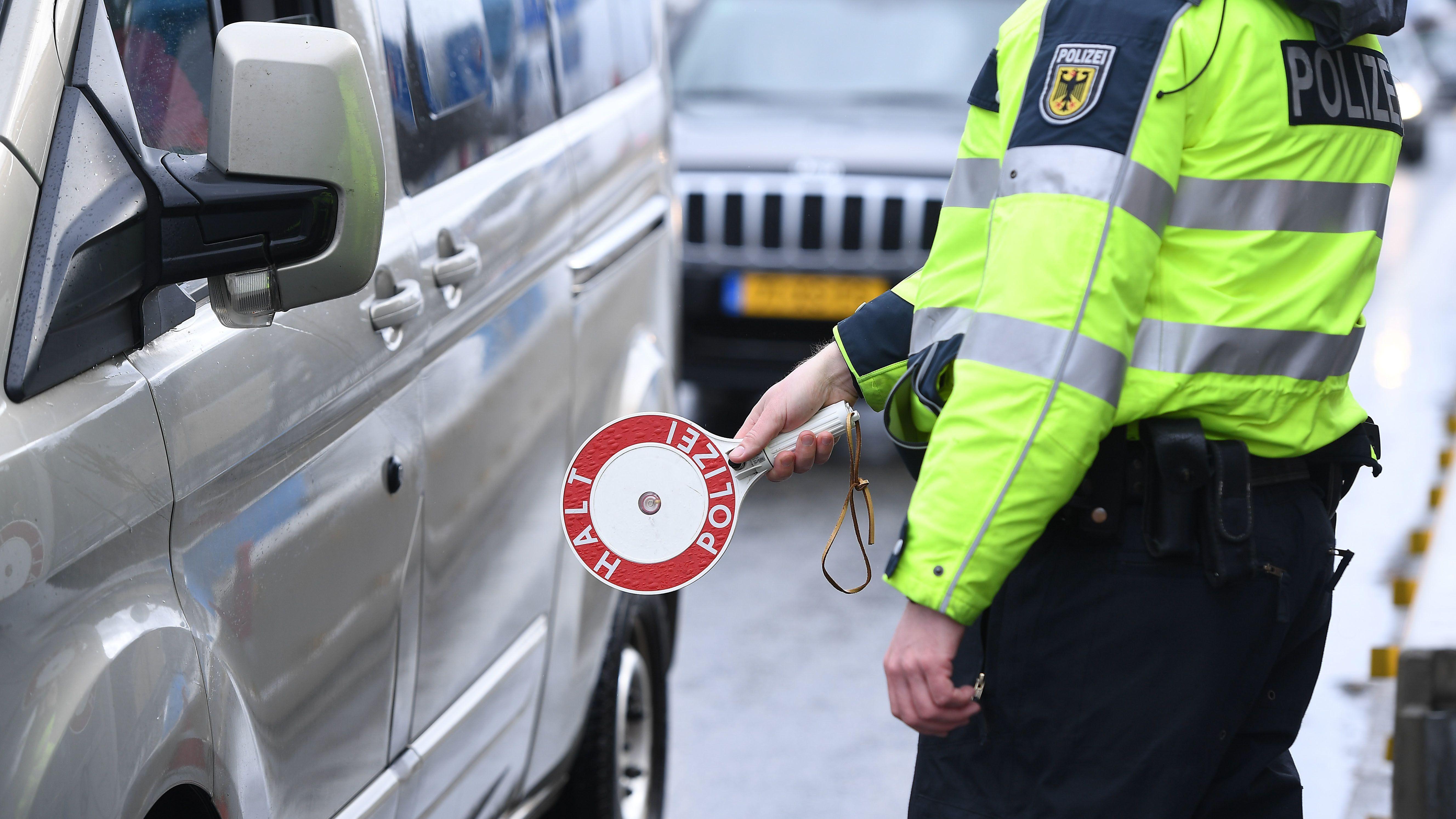 Bundespolizist stoppt ein Auto an der Grenze mit einer Kelle
