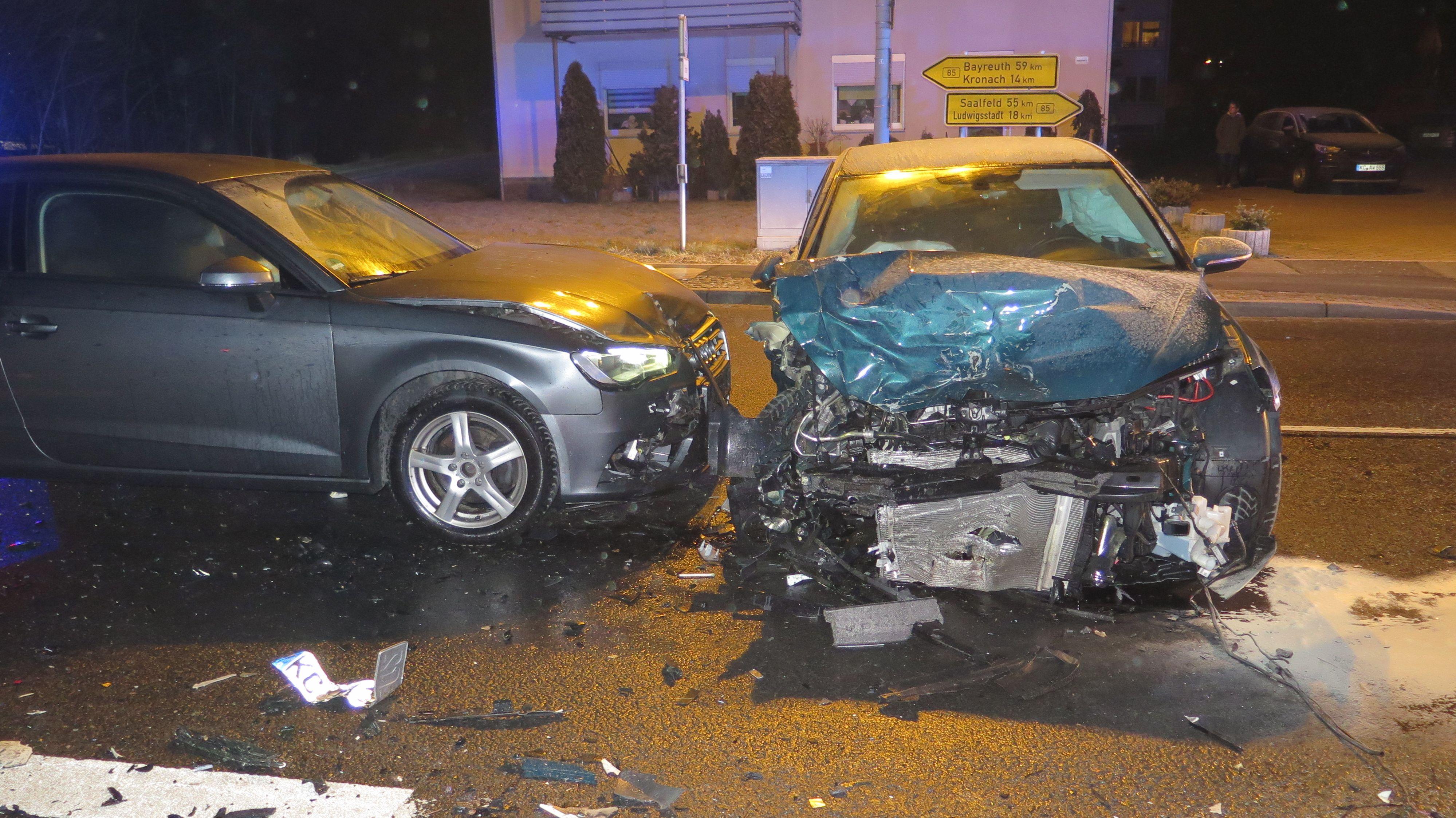 Zwei Autos stehen schwer beschädigt auf einer Straße.