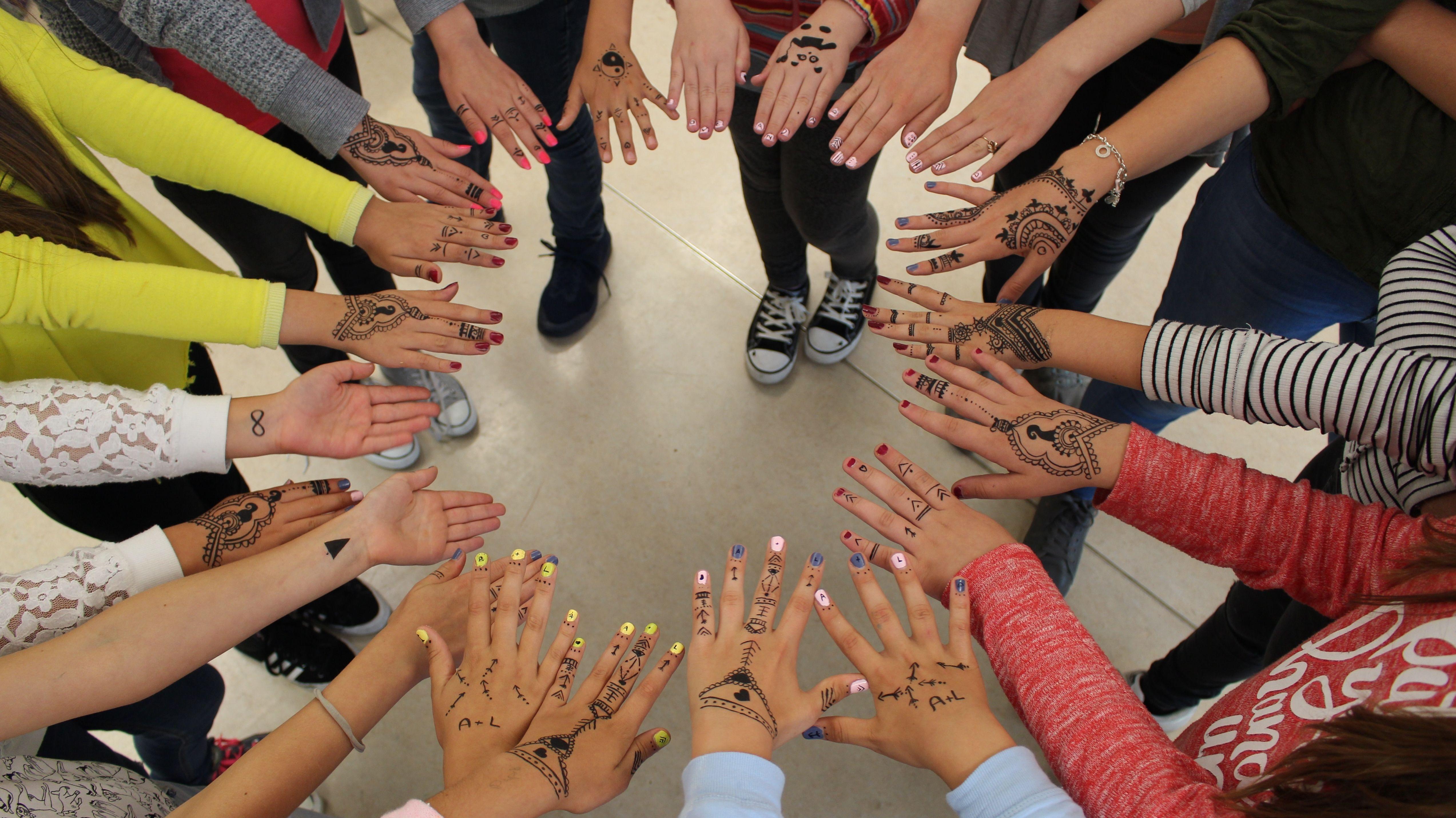 Bemalte Hände von Jugendlichen, die in einem Kreis stehen