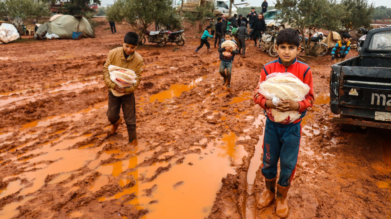 Syrische Kinder waten mit Hilfslieferungen in den Armen durch den Matsch.