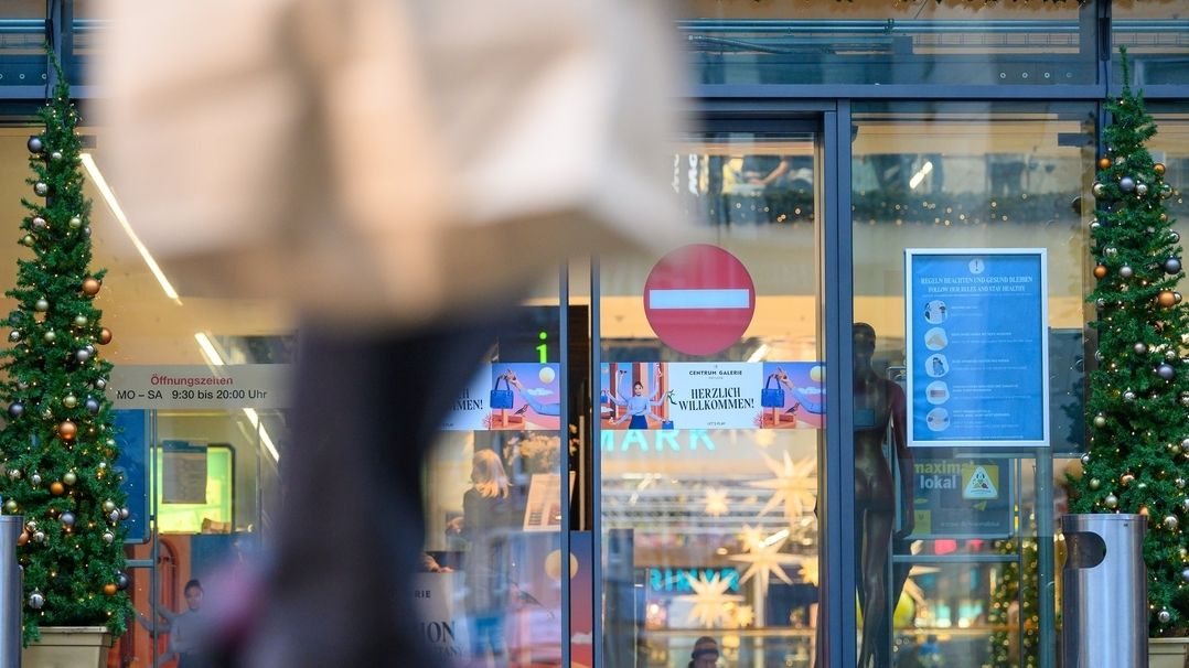 Ein Passant geht mit einer Papiertüte auf Einkaufsstraße entlang