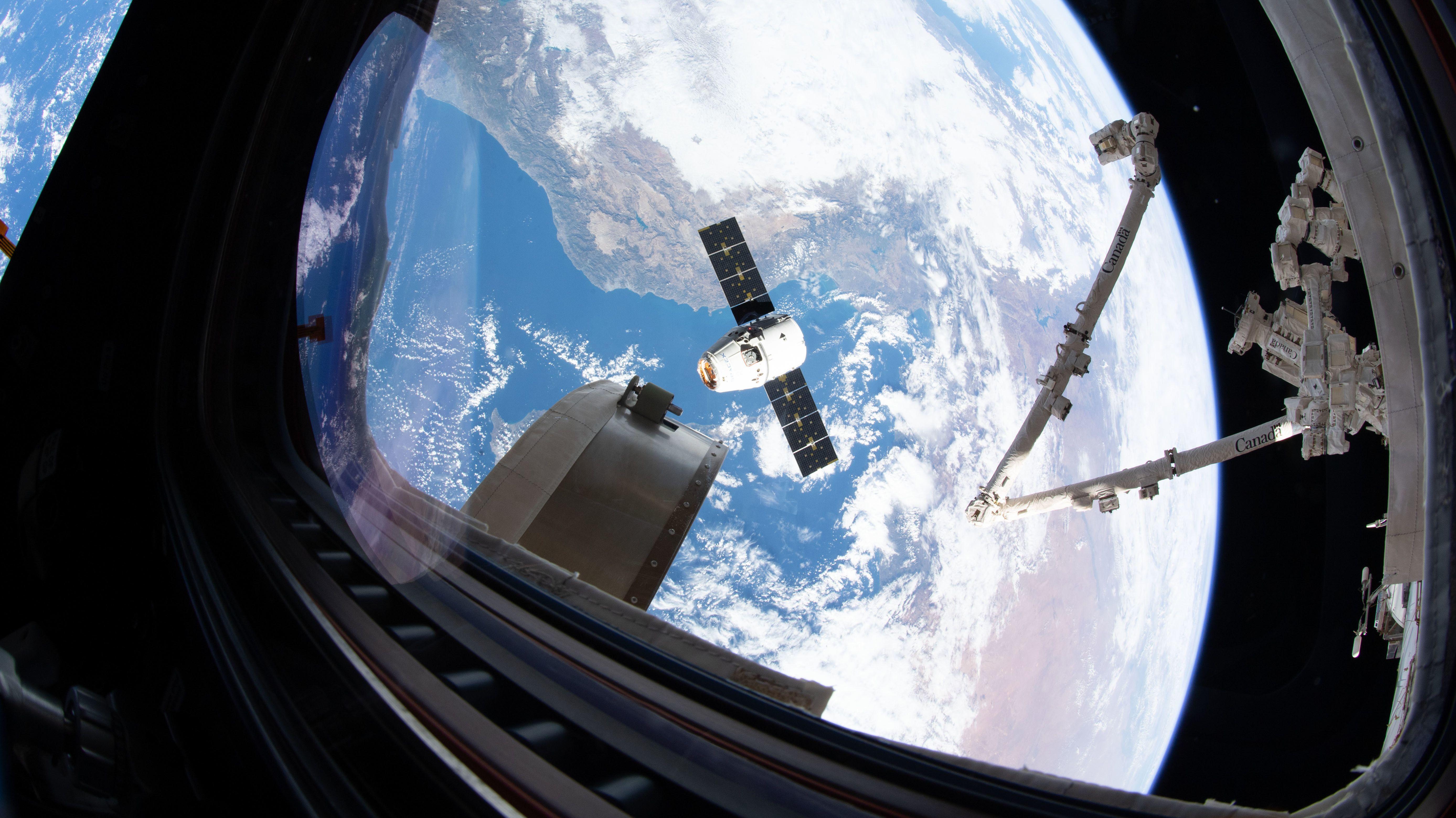 """Blick von der Kuppel der ISS auf die Raumfähre """"Dragon""""."""