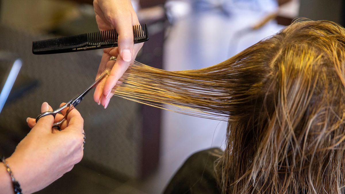 Eine Friseurin in Belgien schneidet einer Kundin die Haare