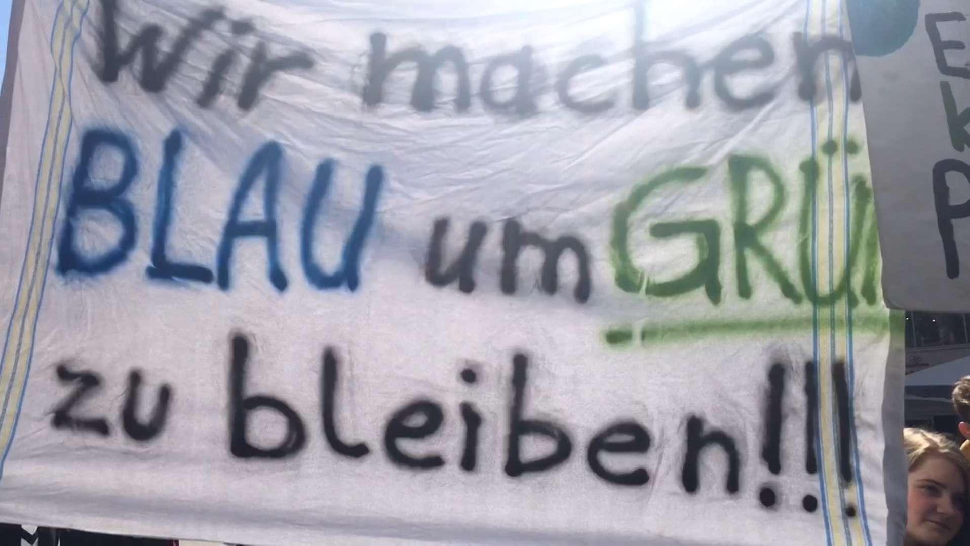 """Plakat bei der """"Fridays for Future""""-Demo in München mit der Aufschrift: """"Wir machen BLAU um GRÜN zu bleiben!!!"""""""