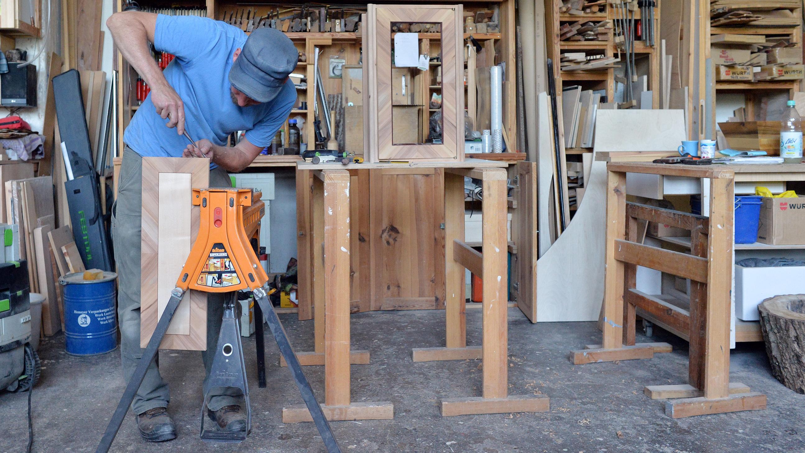 Tischler arbeitet in seiner Werkstatt an einem Wandschrank